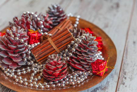 christmas decorations of colored cones sticks beads on a copper tray on a light gray