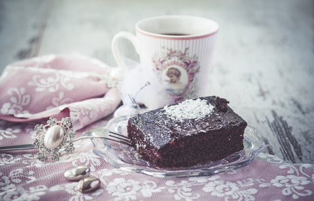 Chocolate brownie cake and coffee on beautiful table with beautiful napkins vintage style. Photo toned with vignette