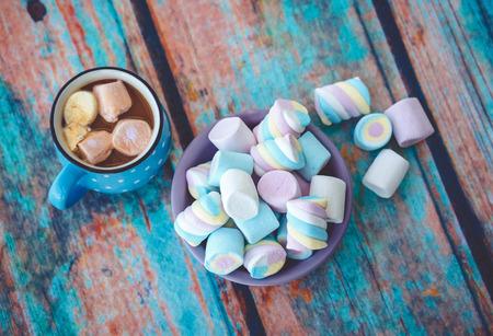 Diferentes tipos de malvavisco en la mesa de madera y una taza de café. Foto entonada con la viñeta. Foto de archivo - 75078646