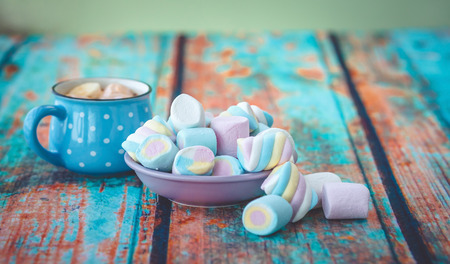 Different kinds of marshmallow on wooden table and cup of coffee. Photo toned with vignette.