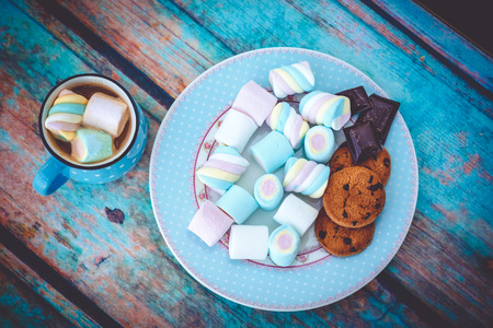 Different kinds of marshmallow, cookies and chocolate on blue plate and cup of coffee. Photo toned with vignette.