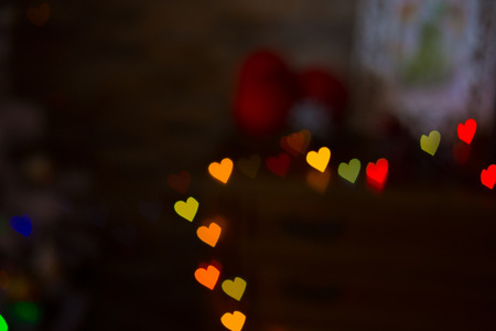 Heart figured New Year's colourful bokeh with blur on dark background Standard-Bild - 97532155