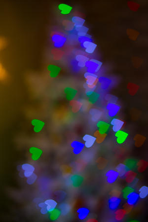 Heart figured New Year's colourful bokeh with blur on dark background Standard-Bild - 97594505