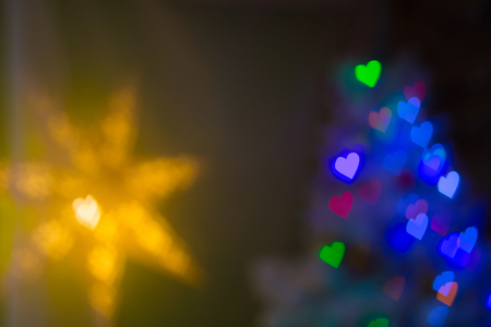 Heart figured New Year's colourful bokeh and star with blur on dark background Standard-Bild - 97387512