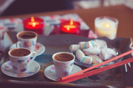 Turkish coffee, marshmallow and cookies on a tray with candles. photos are tinted and with a vignette Standard-Bild - 99796090