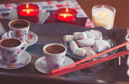Turkish coffee, marshmallow and cookies on a tray with candles. photos are tinted and with a vignette Standard-Bild - 99796093