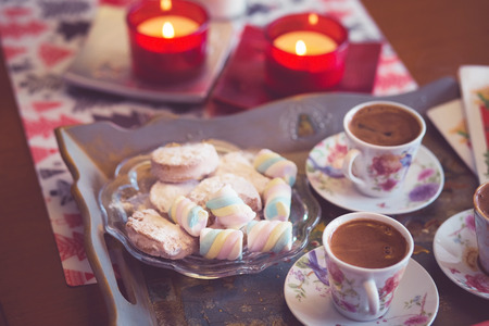 Turkish coffee, marshmallow and cookies on a tray with candles. photos are tinted and with a vignette Standard-Bild - 99729172