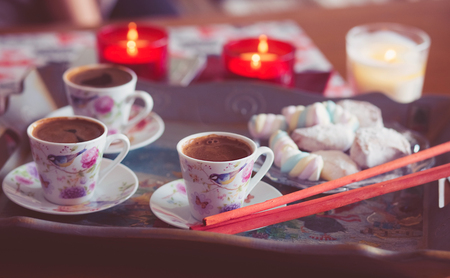 Turkish coffee, marshmallow and cookies on a tray with candles. photos are tinted and with a vignette Standard-Bild - 99737075