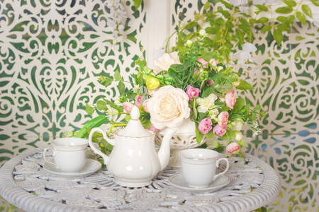 white stylish tea set on a patterned table and flowers Standard-Bild - 105302238