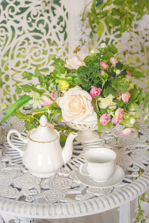white stylish tea set on a patterned table and flowers Standard-Bild - 105302240