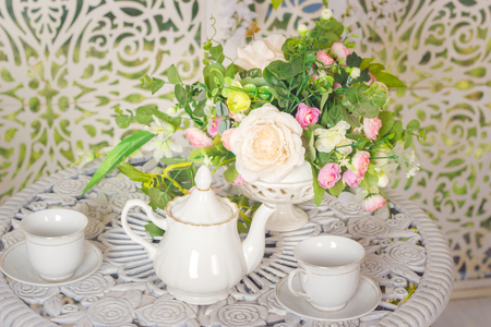 white stylish tea set on a patterned table and flowers Standard-Bild - 105302242
