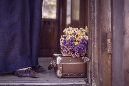 Suitcase, dried flowers and  fragment of female legs in blue trousers and shoes in old train car. Photo tinted in vintage style and with vignette Standard-Bild - 108062943