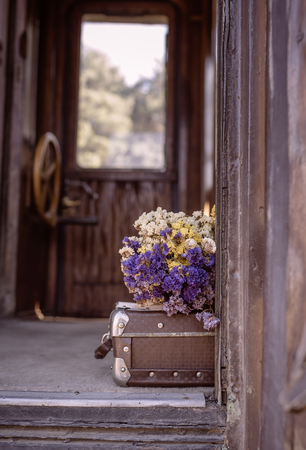Old suitcase and dried flowers in an old train wooden wagon. photo tinted in vintage style and with vignette