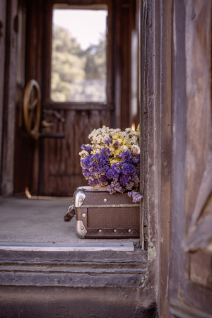 Old suitcase and dried flowers in an old train wooden wagon. photo tinted in vintage style and with vignette Standard-Bild - 108062951