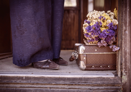 Suitcase, dried flowers and  fragment of female legs in blue trousers and shoes in old train car. Photo tinted in vintage style and with vignette