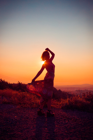 Silhouette of a beautiful young girl on mountain at sunset Standard-Bild - 108062959