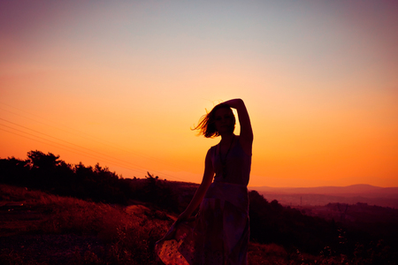 Silhouette of a beautiful young girl on mountain at sunset Standard-Bild - 108062961