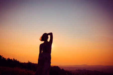 Silhouette of a beautiful young girl on mountain at sunset Standard-Bild - 108062595
