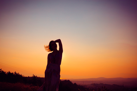 Silhouette of a beautiful young girl on mountain at sunset Reklamní fotografie