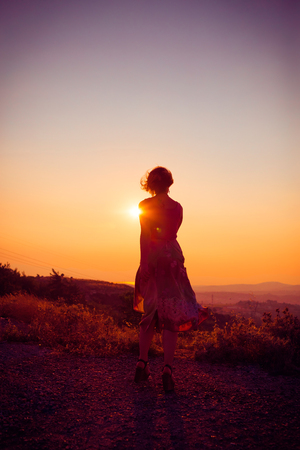 Silhouette of a beautiful young girl on mountain at sunset Standard-Bild - 108062598