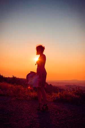 Silhouette of a beautiful young girl on mountain at sunset Standard-Bild - 108062599