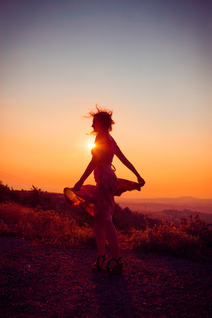 Silhouette of a beautiful young girl on mountain at sunset Stock Photo