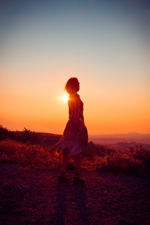 Silhouette of a beautiful young girl on mountain at sunset Standard-Bild - 108062601