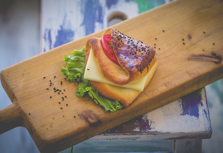 Sandwich with cheese, herbs and tomato on rough wooden board Standard-Bild - 108766405