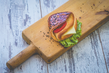 Sandwich with cheese, herbs and tomato on rough wooden board