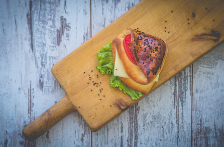Sandwich with cheese, herbs and tomato on rough wooden board Standard-Bild - 108687771
