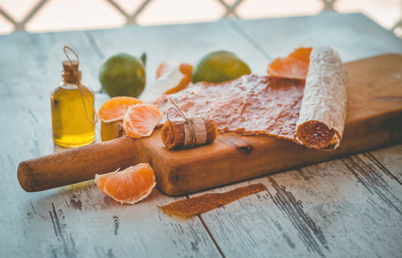 Mandarine pastila on a wooden board on gray wooden table with fruits and small bottle Reklamní fotografie