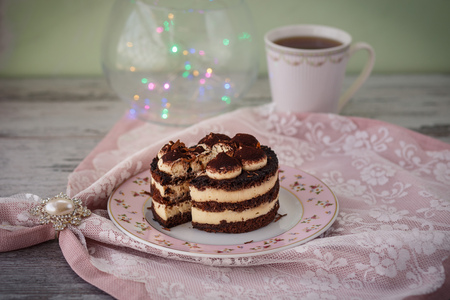 small tiramisu cake with cut piece on plate and cup of tea wooden table with flowers and lights. photo toned and with vignette Standard-Bild - 109878412