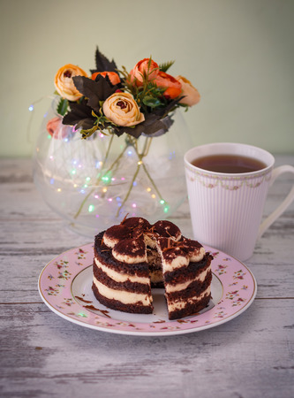 small tiramisu cake with cut piece on plate and cup of tea wooden table with flowers and lights. photo toned and with vignette Standard-Bild - 109878414