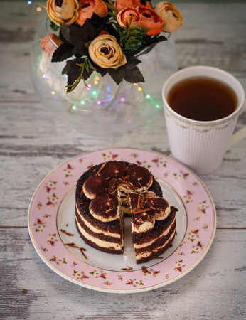 small tiramisu cake with cut piece on plate and cup of tea wooden table with flowers and lights. photo toned and with vignette Reklamní fotografie