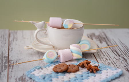 coffee, marshmallow and cookies on gray wooden table. photos are tinted and with a vignette Standard-Bild - 109878428