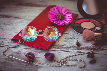 fashionable modern glasses kaleidoscope on wooden table with women accessories