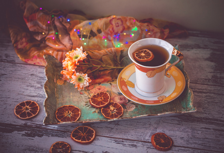 cup of tea with dried orange slices and autumn flowers on a tray and wooden table.