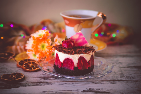 small strawberry cake dusted with grated chocolate on plate, flowers and cup of tea. photo with light effect, toned and with vignette.