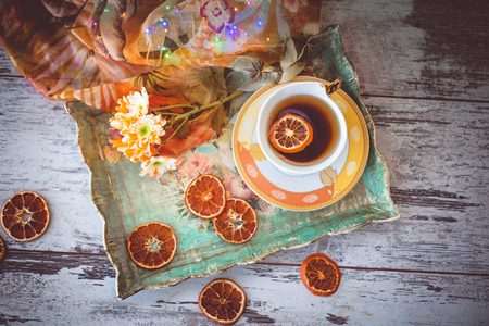 cup of tea with dried orange slices and autumn flowers on a tray and wooden table. photo toned and with vignette. Reklamní fotografie