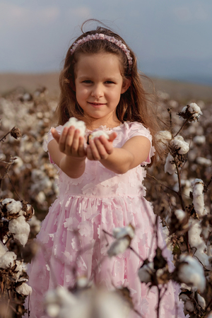 Beautiful little girl with long hair and in pink dress in cotton field.focus on model face
