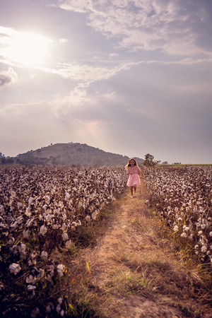 Beautiful little girl with long hair and in pink dress girl running in cotton field