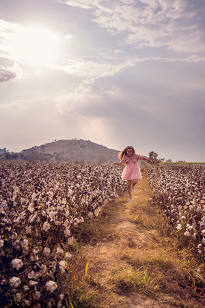 Beautiful little girl with long hair and in pink dress girl jumping in cotton field.