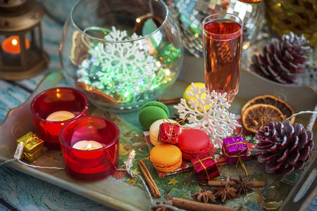 Christmas still life with  glass of wine, macaroons, candles, dried fruit and spices. Photo tinted and with vignette, with lights and bokeh.