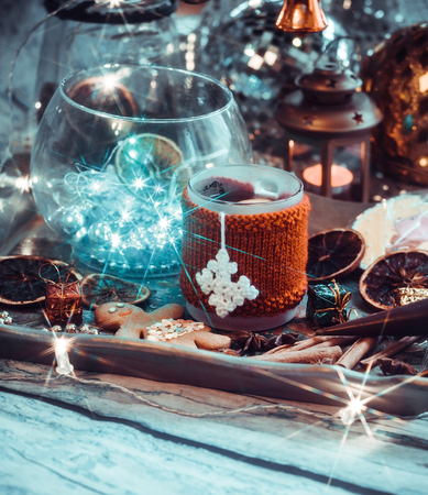New Years still life with mug of tea with knitted cup cover, cookies, chocolate, dried fruit and seasonings with lights and bokeh. Photo toned and with vignette