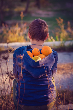 Sitting boy in  blue sweater with hood filled with oranges Reklamní fotografie