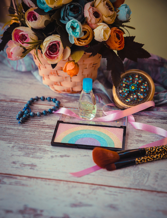 Highlighter on gray wooden table with flowers, tassels, mirror and silk scarf. Photo tinted and with vignette