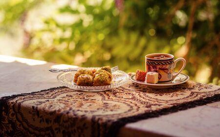 Café turco, baklava y delicias turcas en la mesa. Foto tonificada y poca profundidad de campo.