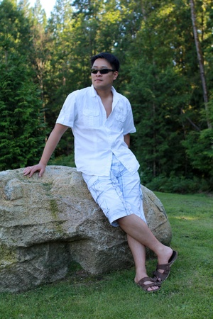 sandal tree: Young Asian man wearing sunglasses leaning on a stone