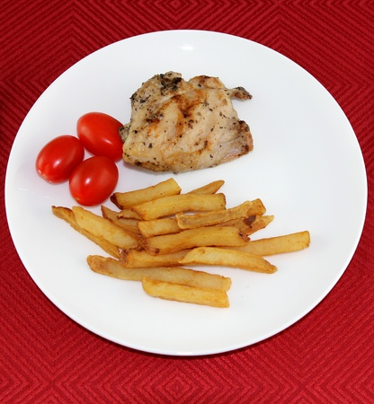 red tablecloth: Chicken combo dish with fried potatoes and tomatoes on a red tablecloth Stock Photo