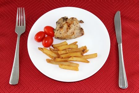 red tablecloth: Dish on a red tablecloth with flatware